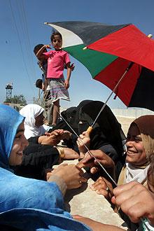Palestinske og egyptiske slektninger hilser på hverandre. Foto: AP/Scanpix