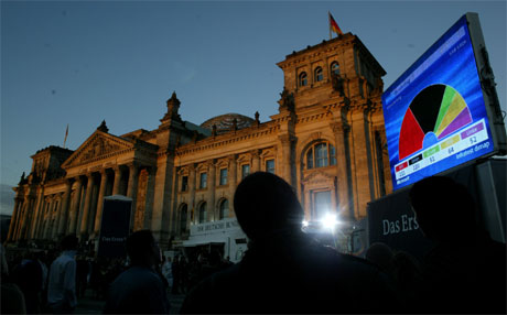 Velgerne har talt, og nå grubler politikerne og kommentatorer over hva de sa. Her vises valgdagsmålingen på storskjerm utenfor riksdagsbygningen i Berlin. (Foto: Julian Stratenschulte/AP/Scanpix)