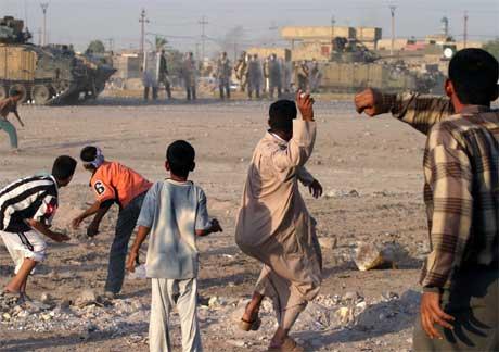 Irakere kaster stein mot britiske soldater i forbindelse med dagens sammenstøt mellom britiske og irakiske soldater i Basra. (Foto: Scanpix / Reuters)