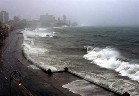 Bølger slår over strandpromenaden El Malceon i Havana. Innbyggerne holder seg imidlertid innendørs til
