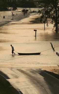 En mann drar en robåt over Route 45 i Louisiana sør for New Orleans. (Foto. R.Beck, AFP)