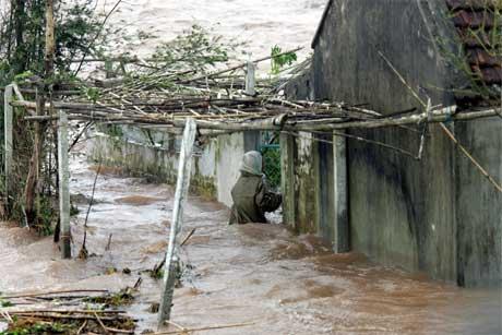 En bonde prøver å redde eiendeler fra det oversvømmede hjemmet sitt i Nam Dinh-provinsen i Vietnam. Bare i dette landet har 300.000 mennesker måttet flykte fra hjemmene sine på grunn uværet. (Foto: Hoang Dinh/ AFP/ Scanpix)