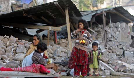 En familie ved sitt sammenraste hus i Muzaffarabad. Regn og kulde setter de overlevende på nye prøvelser. (Foto: A.Masood, Reuters)