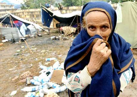Ei eldre kvinne dekkjer til nasa for å sleppe lukta som ligg over denne provisoriske flyktningleiren. (Foto: AFP/Scanpix)
