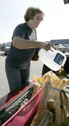 """I Florida har folk begynt å forberede seg på orkanen """"Wilma"""". Denne kvinnen har hamstret vann og mat. (Foto: AP/Scanpix)"""