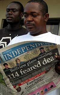 En nigerianer leser om flyulykken i dagens avis. (Foto: AP/Scanpix)