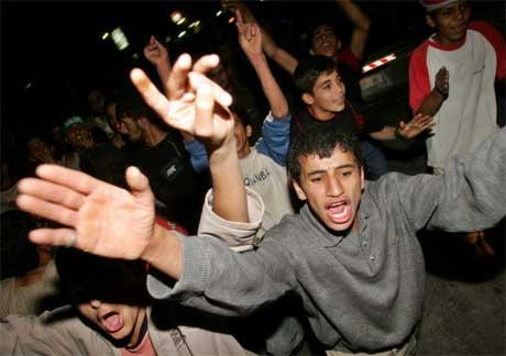 Jublande palestinarar samle seg i går kveld utanfor heimen til sjølvmordsbomaren som tok med seg fem menneske i døden i Hadera i Israel i går. (Foto: Reuters/Scanpix)