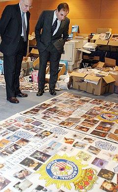 Politidirektør Victor Garcia Hidalgo (t.v.) og Spanias innenriksminister Jose Antonio Alonso studerer beslaglagte DVD-plater og CD-er på en politistasjon i Madrid. Foto: Scanpix.