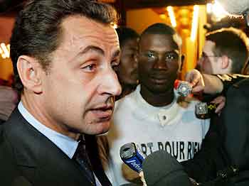 Innenriksminister Nicolas Sarkozy snakker til pressen. Ved siden av Ahmad, en representant for ungdommene. Foto: Joel Saget, AFP