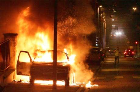 En bil i full fyr på Pierrefitte-gaten nord i Paris i natt. (Foto: Scanpix / AP)