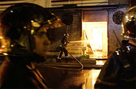 Brannmannskaper slukker en brann i et hus i Aubervilliers, nord for Paris i natt. (Foto: Scanpix / AP)
