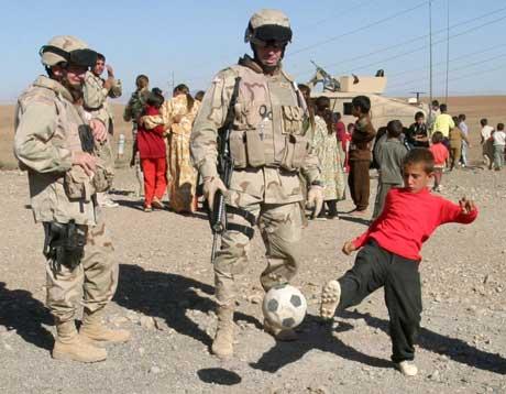 Amerikanske soldater spiller fotball med en gutt i Mosul. (Foto: Scanpix / AP)