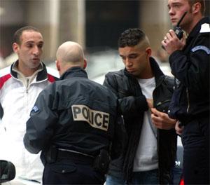 Politimenn sjekker identitetspapirer til to forbipasserende ved Champs Elysees. (Foto; Mehdi Taamallah/AP/Scanpix)