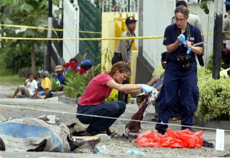 Australske politifolk gransker et tøystykke som ble funnet ved huset der en malaysisk terrormistenkt i forrige uke ble drept i en skyteepisode. (Foto: Crack Palinggi/Reuters/Scanpix)