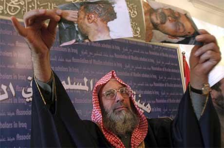 Denne aktivisten holder fram et bilde av en mann som skal ha blitt torturert til døde. (Foto: Reuters/Scanpix)