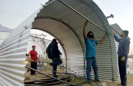 Pakistanske frivillige planlegger å sette opp 300 slike bølgeblikkskur i jordskjelvområdene hver dag. (Foto: A.Hassan, AFP)