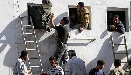 EGYPT: Velgere bruker stiger for å ta seg inn i et valglokale i Bosat nord for Kairo. Foto: Amr Nabil, AP