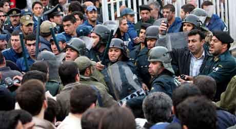 TEHERAN: Opprørspoliti forsøker å hindre folk fra å ta seg inn i boligblokka som ble truffet av ulykkesflyet. Foto: Hasan Sarbakhshian, AP