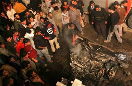 Ei menneskemengde har samla seg ved vraket av bilen som vart utsett for angrepet. (Foto: AP/Scanpix)