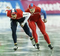 Even Wetten (til høyre) klusser med vekslingen fra indre til yttre bane og må vike for Simon Kuipers på 1500 meter i verdenscupen på skøyter i Torino søndag. Wetten ble dermed diskvalifisert. (Foto: Erik Johansen / Scanpix)