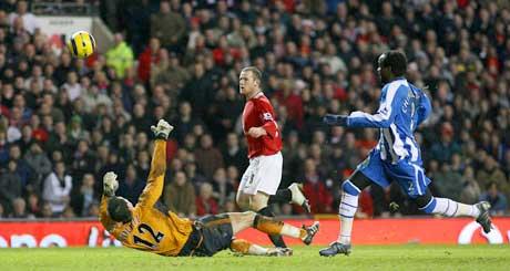 Wayne Rooney lobber over Wigan-keeper Matt Pollitt til 3-0. (Foto: Reuters/Scanpix)