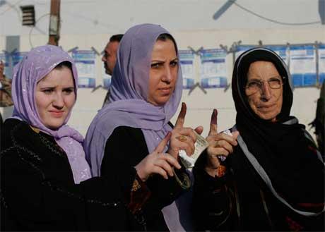 Velgere i Bagdad viser frem blekket på fingrene som tegn på at de har stemt. (Foto: Samir Mizban/ AP/ Scanpix)