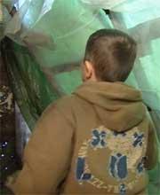 Denis Omeri i huset dekket av presenning (Foto: Berit Heggholmen, NRK)