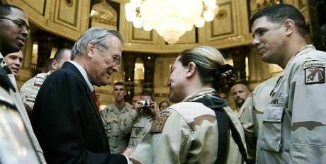 MER TRENING: Donald Rumsfeld sa samtidig at antall soldater som er involvert i treningen av irakiske styrker, skal økes. Her hilser han på soldater i Al Faw-palasset i Bagdad. (Foto: Scanpix / AP / Jim Young, Pool)