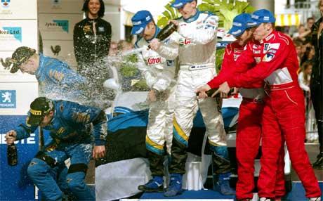 Under premieutdelingen i rally Finland i 2003 fikk Petter Solberg som kom på en andreplass en sjampanjedusj av Richard Burns som kom på tredjeplass og vinneren Markko Märtin. (Foto: AFP /LEHTIKUVA/VILLE MYLLYNEN)