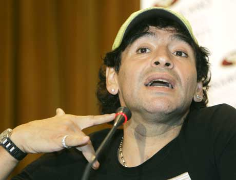 Diego Maradona viser hvor den brasilianske politimannen angivelig skal ha holdt pistolen mot ham på flyplassen. (Foto: AP/Scanpix)