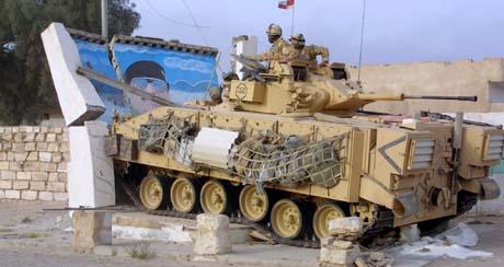 Et pansret britisk kampkjøretøy kjører inn i et bilde av Saddam Hussein i Basra. (Foto: M.Richards, Reuters)