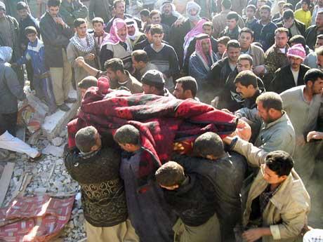 Et av de døde familiemedlemmene bæres bort. Foto:Scanpix/AFP.