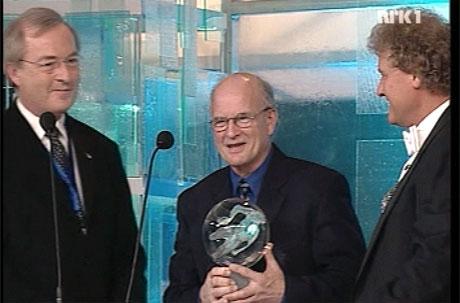 Sverre Øfstaas mottar ildsjelprisen av idrettspresidenten under Idrettsgallaen i Hamar. Til høyre står programleder Dan Børge Akerø. (Foto: NRK)