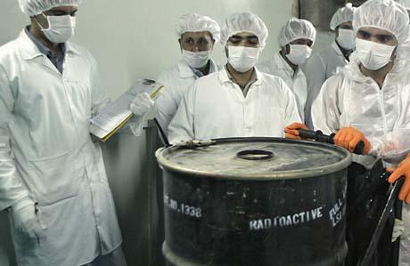 Seglet brytes: Tekniskere flytter en tønne med radioaktivt uran, forseglet av IAEA. (Foto: B.Mehri, AFP)