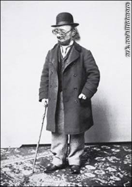 Ole Johan Larsen står modell for den nye Ibsen-mynten, i Norges Banks lokaler.