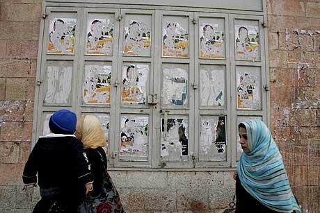 Palestinske kvinner går forbi ødelagte valgplakater i Øst-Jerusalem. Foto: AFP/Scanpix