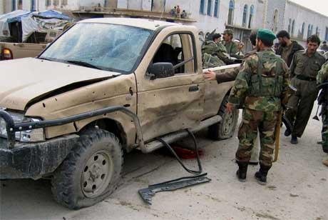 Soldater sjekker stedet fire mennesker ble drept i en bombeeksplosjon i Kandahar. (Foto: Noor Khan/ AP/ Scanpix)