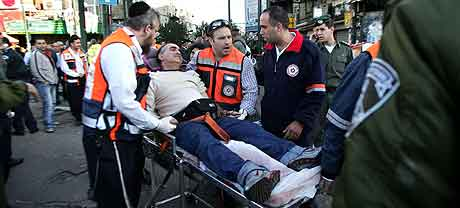 Redningsarbeidere tar seg av en av de sårede i Tel Aviv. Foto: Ariel Schalit, AP