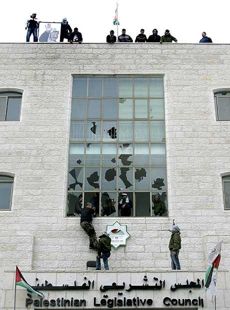 Væpnede Fatah-tilhengere reiser det palestinske flagget på taket av parlamentsbygningen i Ramallah på Vestbredden. (Foto: AFP/Scanpix)