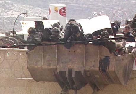 En gruppe opprørspoliti entrer taket på en okkupert bygning. (Foto: IBA)