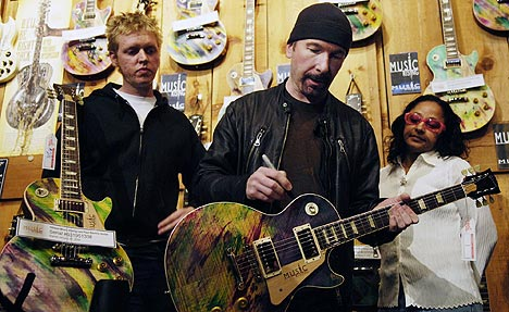 John Henry Kelly, som fikk sitt studio ødelagt i orkanen Katrina, ser på at The Edge fra U2 signerer en gitar på The Guitar Centre i Los Angeles. Foto: Chris Pizzello, AP Photo / Scanpix.