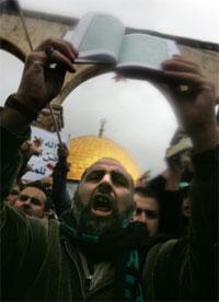 En palestiner roper mens han holder opp Koranen foran Al-Aqsa moskeen i Jerusalem. Foto: AFP Photo