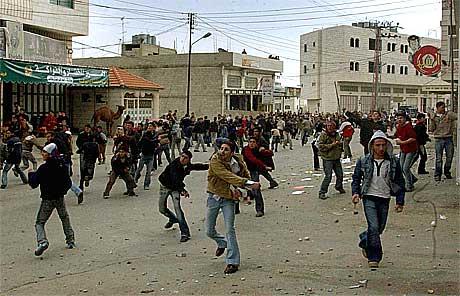 Palestinske ungdommer kaster stein mot hovedkvarteret til observatørstyrken i Hebron.(Foto:AP/Scanpix)