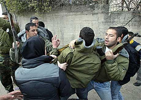 Palestinske sikkerhetsstyrker tar hånd om en av de steinkastende ungdommene.(Foto:Reuters/Scanpix)