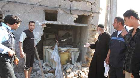Innbyggere og politifolk ved et utbombet hjem i Bagdad, der tre mennesker ble drept i dag, deriblant et barn. (Foto: AP/Scanpix)