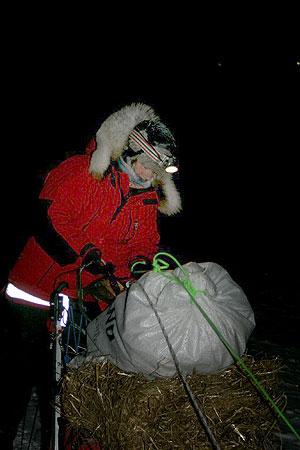SKOGANVARRE: Elisabeth Edland legger ut halm til hundene foran en hvil.