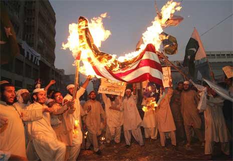 Demonstrantene ropte slagord og brente flagg i Karachi i Pakistan i dag, i protest mot Muhammed-tegningene. (Foto: Reuters/Scanpix)