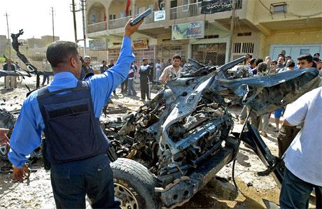 Volden i Irak krever nye ofre hver dag. Her forsøker en irakisk politimann å holde orden etter en bilbombeeksplosjon i Bagdad i dag. (Foto: Ahmad Al-Rubaye/AFP/Scanpix)