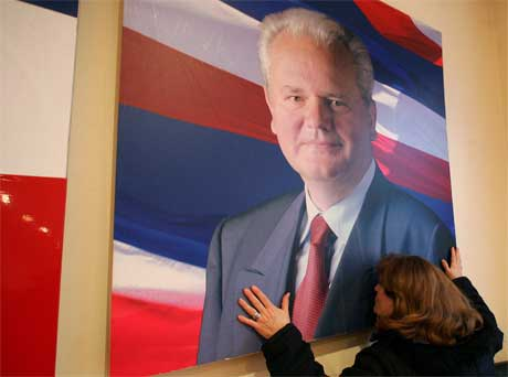 En tilhenger kysser bildet av Slobodan Milosevic i Beograd i dag. Foto: AP/Scanpix