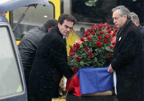 Kisten med Slobodan Milosevic ble tatt imot av partikamerater på flyplassen i Beograd i dag. (Foto: Srdjan Ilic/AP/Scanpix)